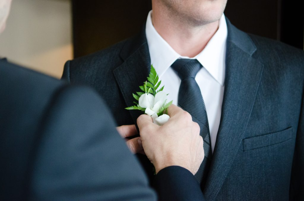 Best man pinning Boutonniere on groom before the wedding