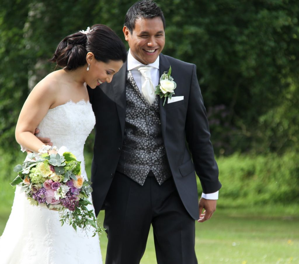 Newly married Bride and Groom outside on a green landscape