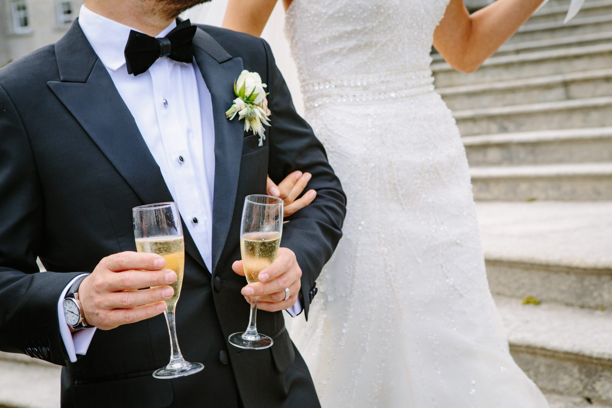Groom wearing tuxedo holding champagne glasses with bride on his arm