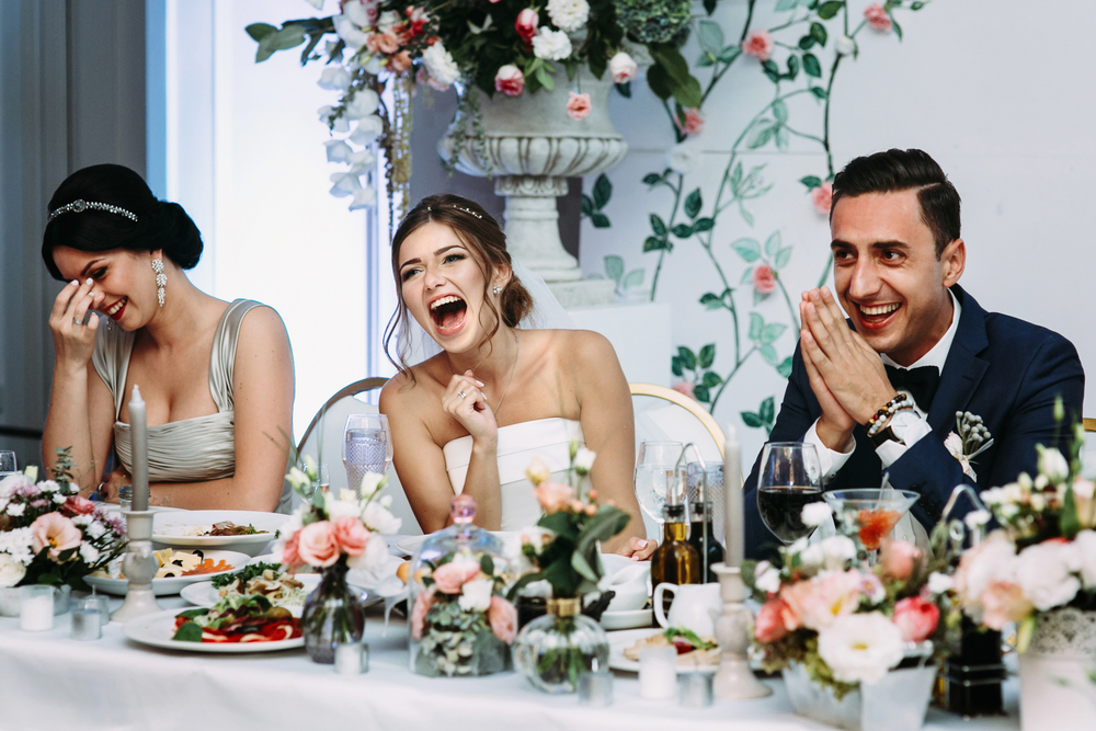 bride and groom laughing at maid of honor toast