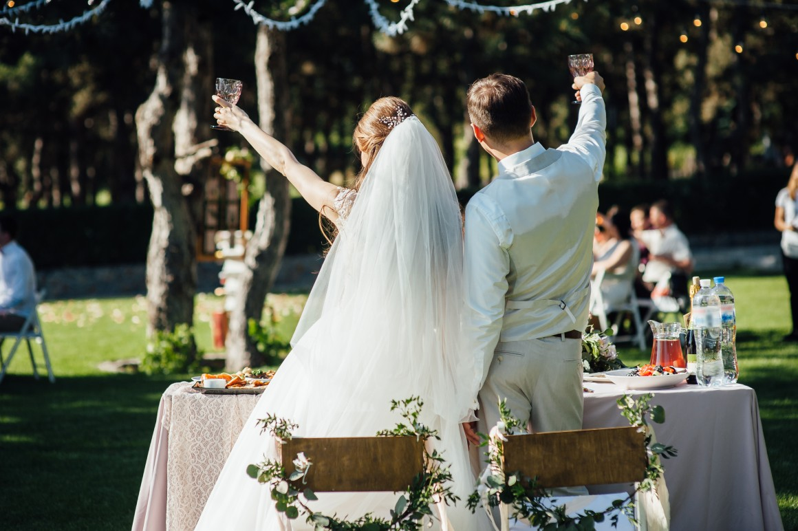 bride and groom raise glasses to toasts guests at outdoor wedding