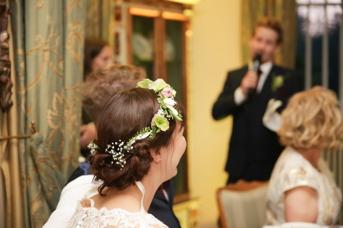 Bride with flower crown and groom listen to best man speech at wedding
