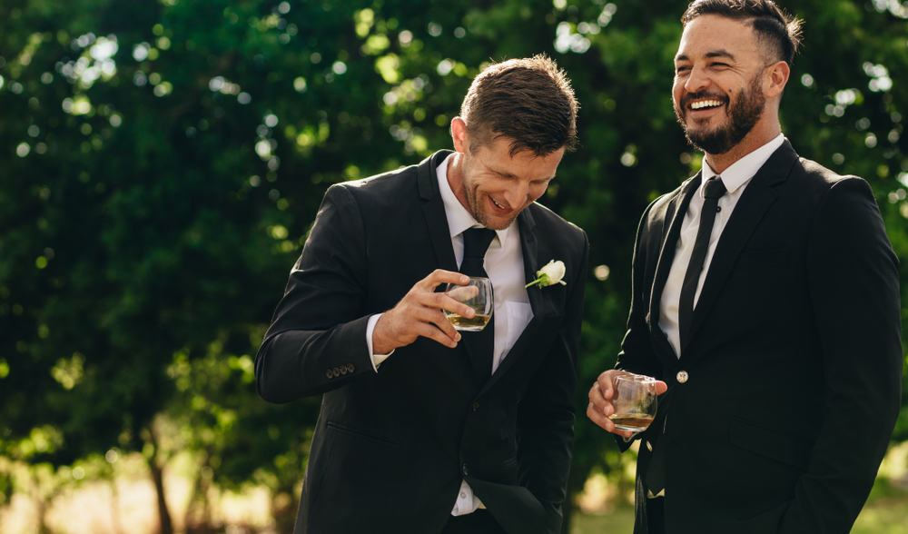 Groom and brother in black suits laugh while sipping on a cocktail at outdoor wedding