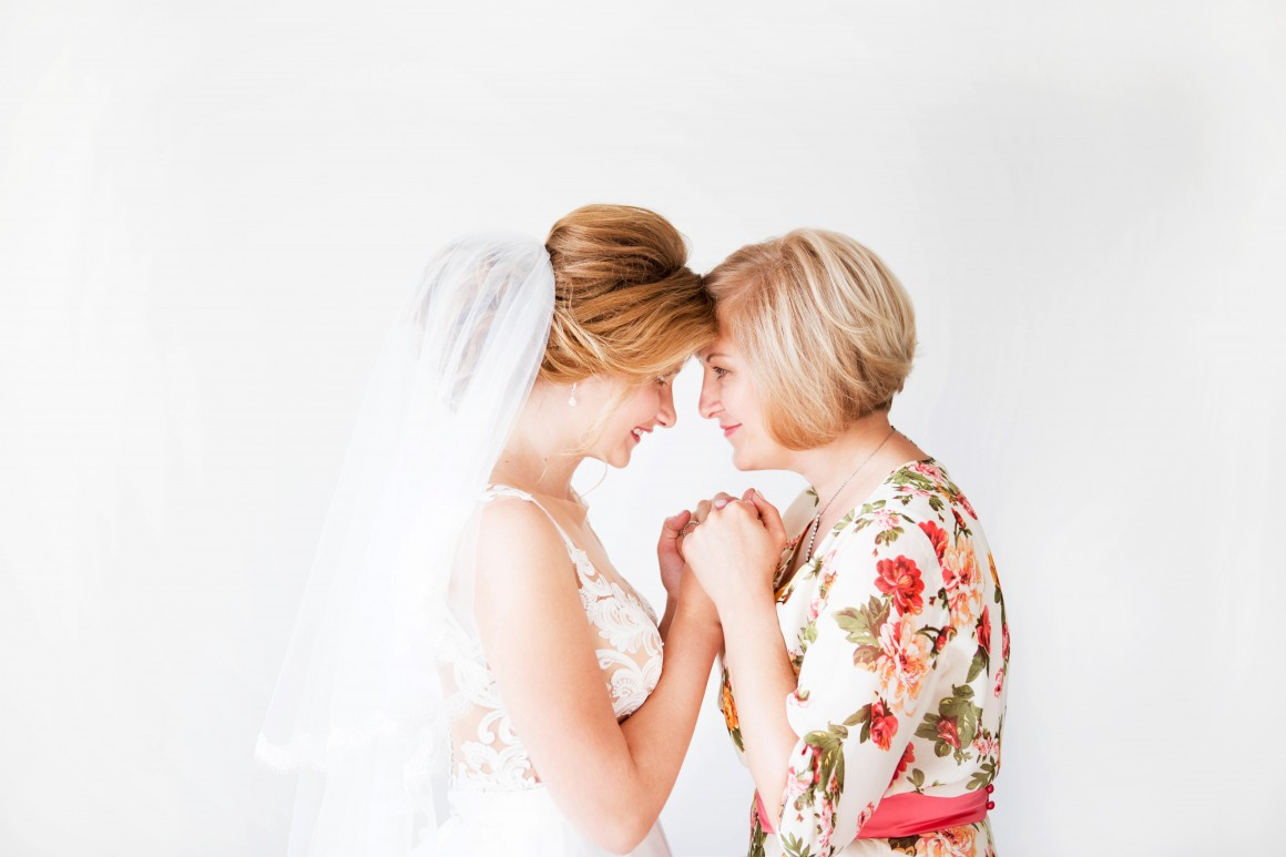Mother embracing daughter at her wedding.