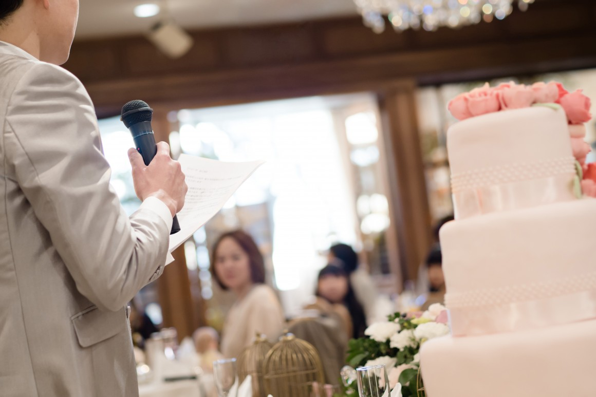 Groom in tan suit standing next to ivory wedding cake delivering speech.