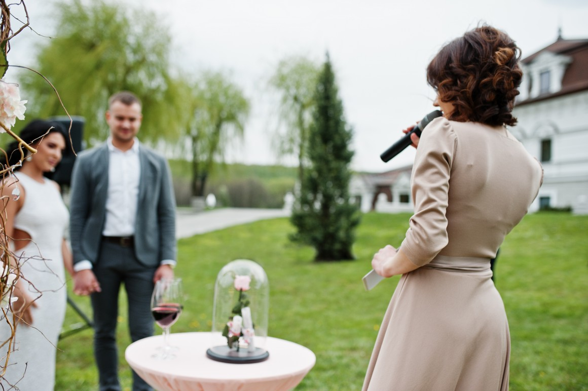 Woman giving speech to bride and groom at outdoor wedding
