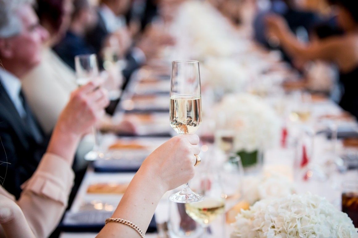 Wedding guests at table raise champagne glasses to toast newlyweds