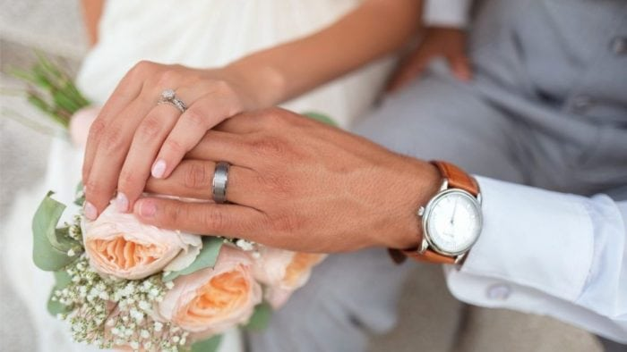 Picture of Bride and Groom Hands Intertwined with Wedding Bands Featured