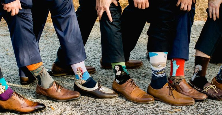 Set of groomsmen wearing socks with different famous paintings