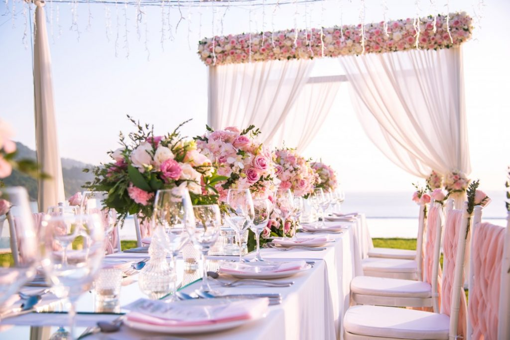 outdoor wedding reception table with pink linens, flowers and tableware