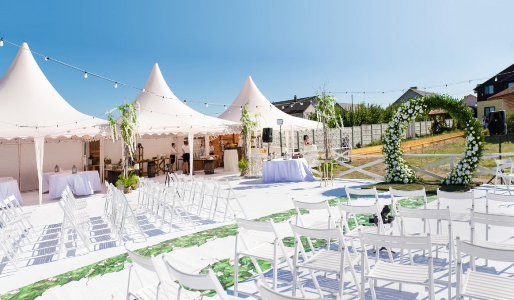 outdoor wedding ceremony with empty white chairs and tents