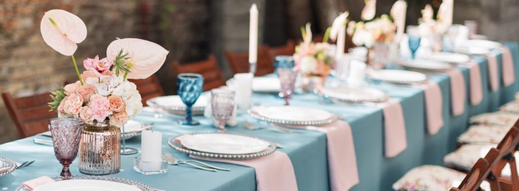 long wedding reception table with blue linen and table settings