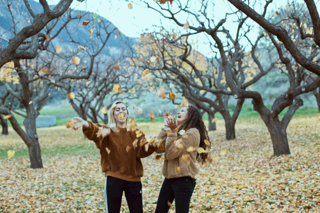 two girls laughing and throwing leaves