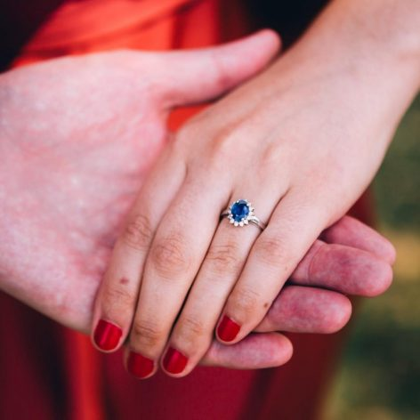 woman wearing sapphire ring holding hands