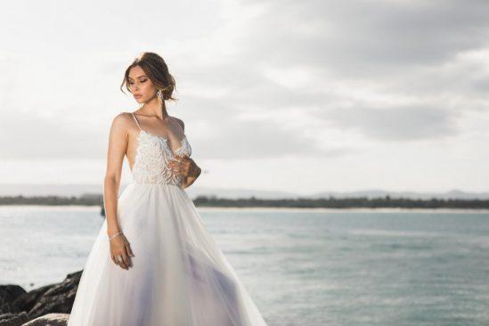 woman standing beside water in wedding dress