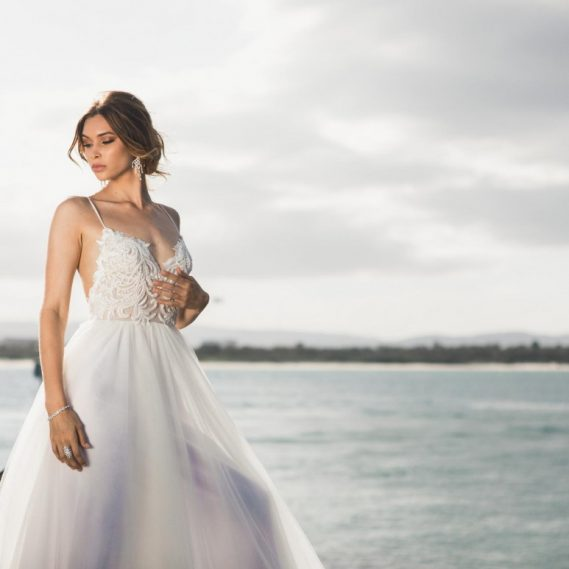 woman standing beside water in wedding dress