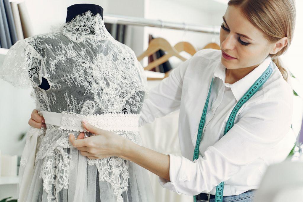 Seamstress measuring wedding dress