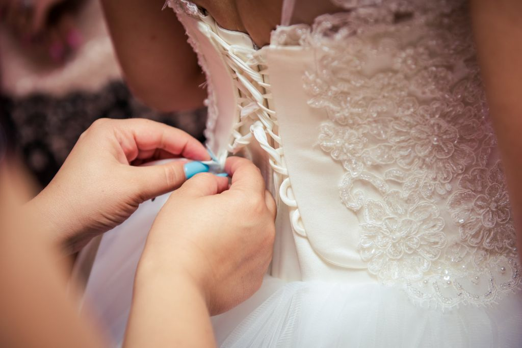 Bride having her dress fitted