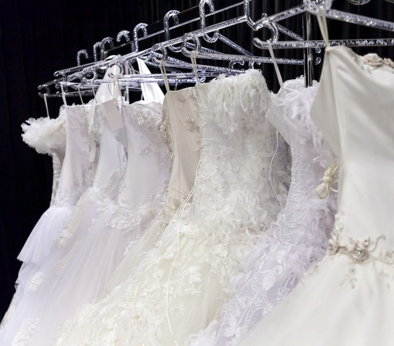Various wedding dresses on coat rack