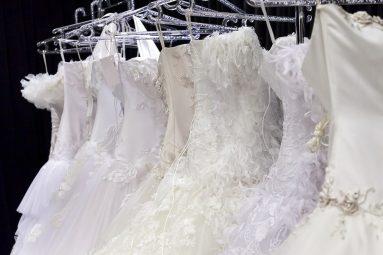 Various wedding dresses on coat rack