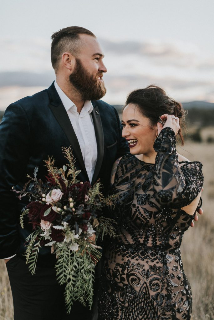 bride wearing beaded black wedding dress laughing while groom embraces her at outdoor wedding