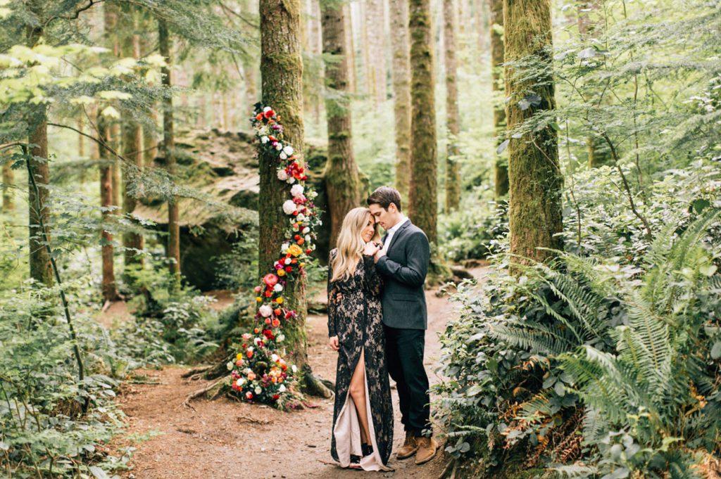 boho bride wearing black lace wedding dress standing with groom at Rattlesnake Ridge outdoor wedding