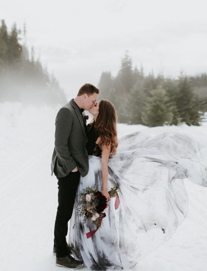 Bride wearing black wedding dress with painted skirt kissing groom in the snow.