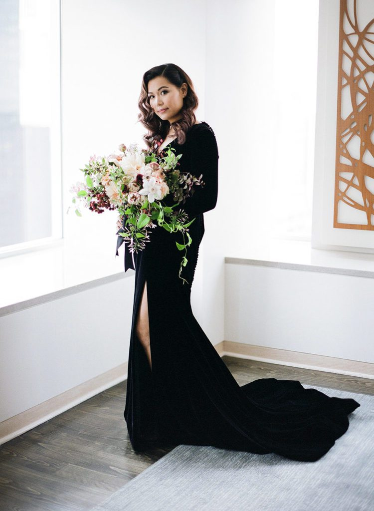 Bride wearing a sophisticated black long sleeve wedding dress with oversized bouquet