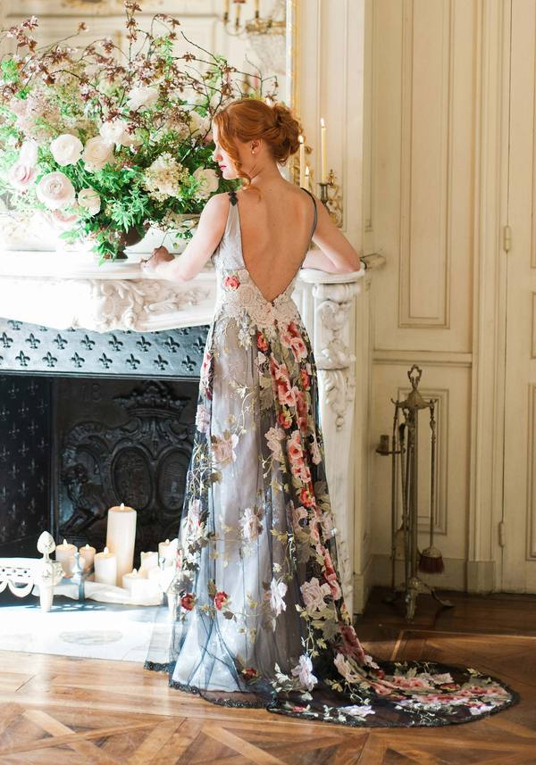 bride standing by fireplace wearing a black wedding dress with floral appliques