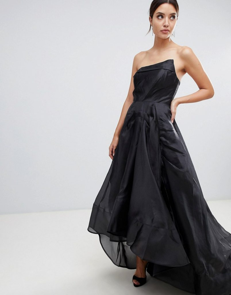 Woman modeling black wedding dress with asymmetric strapless neckline and hi lo skirt