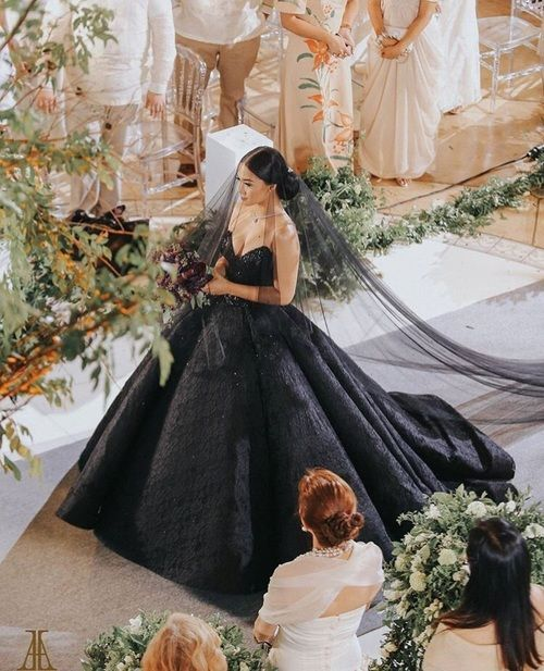 beautiful bride floats down the aisle in a dramatic black ballgown and black veil at elegant traditional wedding