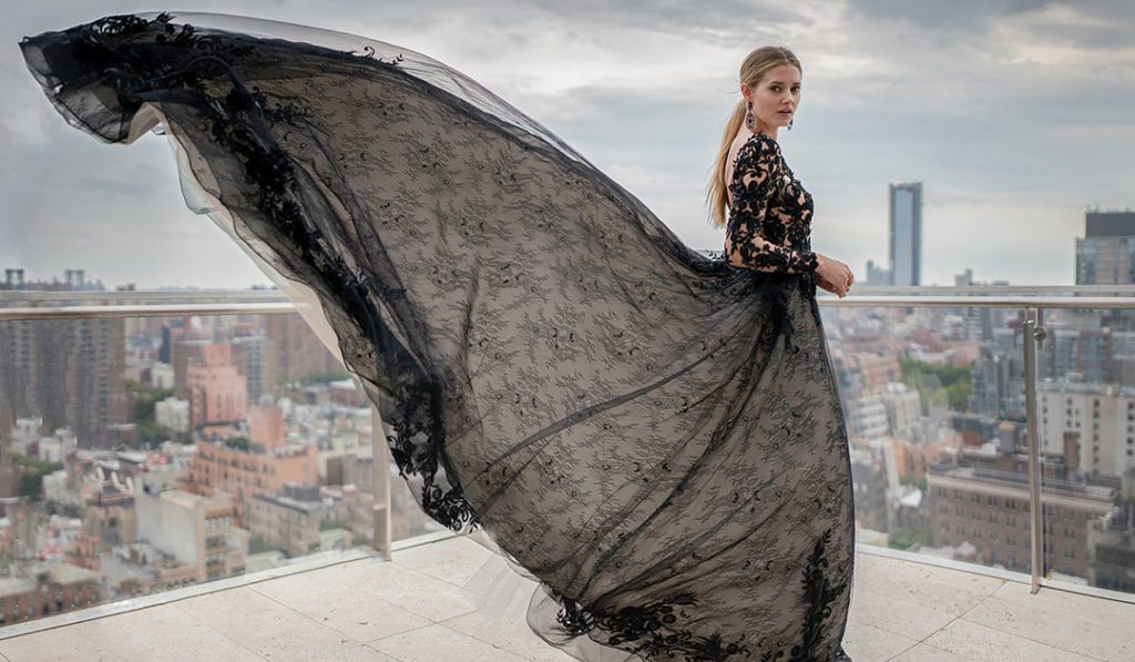 Model on rooftop wearing nude and black lace wedding dress by Maggie Sottero