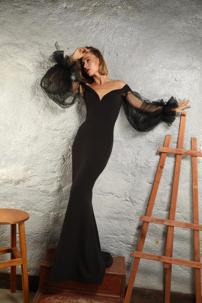 woman wearing sexy fitted black off the shoulder dress with billowy sheer sleeves