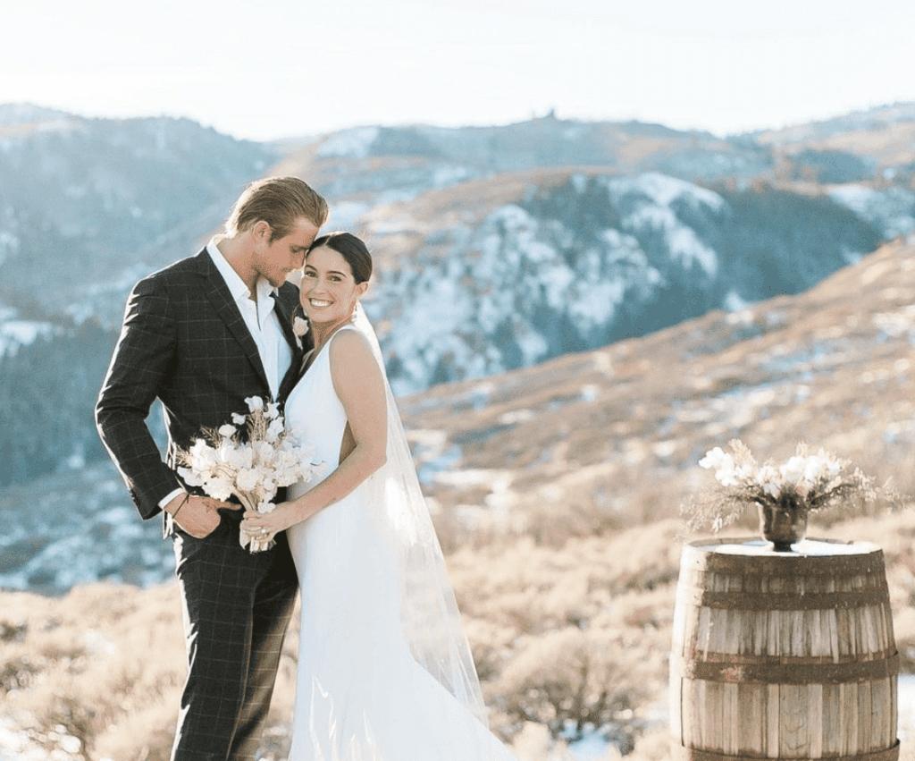 Lauren Dear and Alexander Ludwig embrace on wedding day on hillside