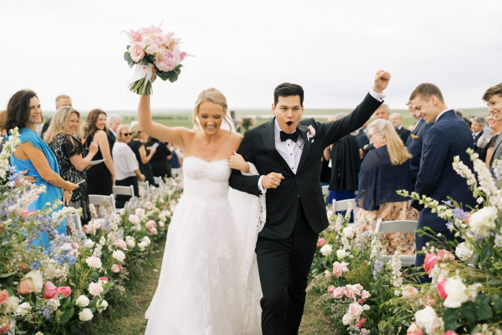Alex Drummond and Mauricio celebrating while walking down aisle after saying I do