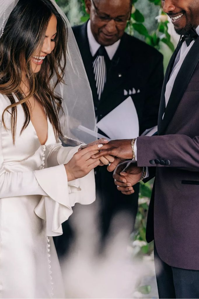 Erin Lim putting wedding band on Joshua Rhodes as they tie the knot