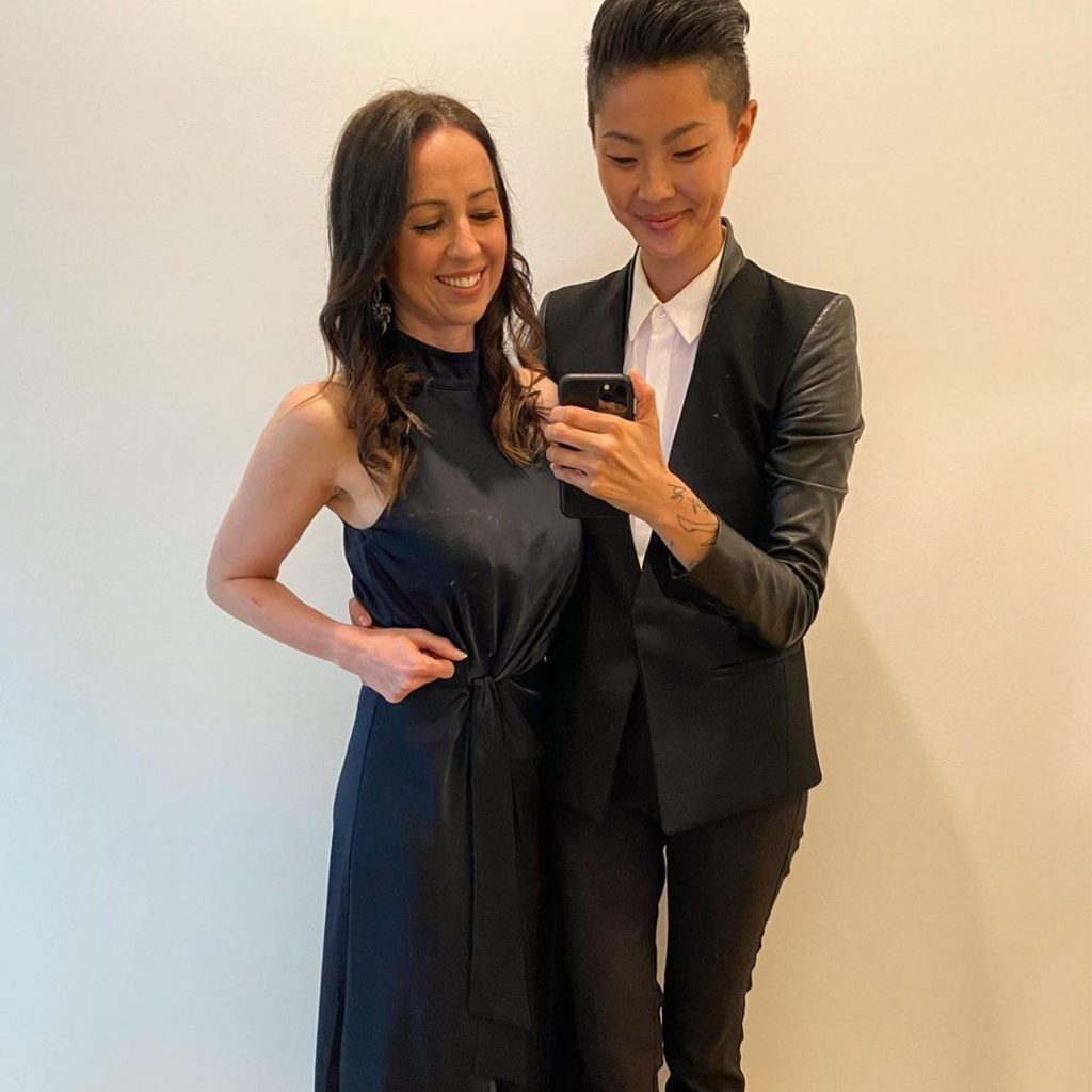 Top Chef's winner Kristen Kish and Bianca Dusic dressed in black holding phone at wedding