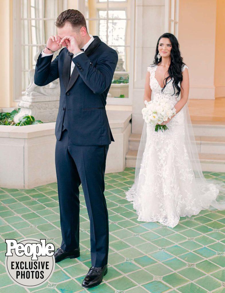 Adam Gottschalk crying during first look before wedding ceremony. Bride Raven Gates wearing beautiful lace wedding dress