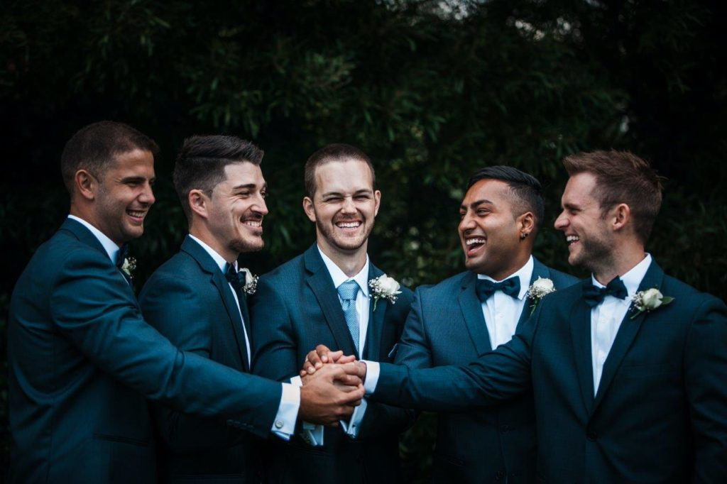 Groom and groomsmen join hands to celebrate wedding day