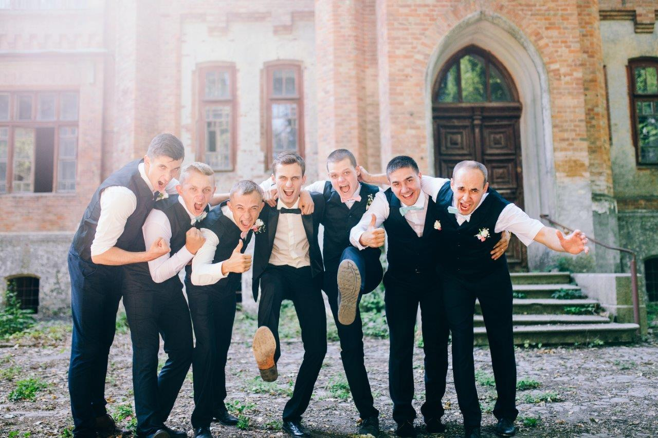 Groom kicking up shoes with arms around groomsmen celebrating wedding day