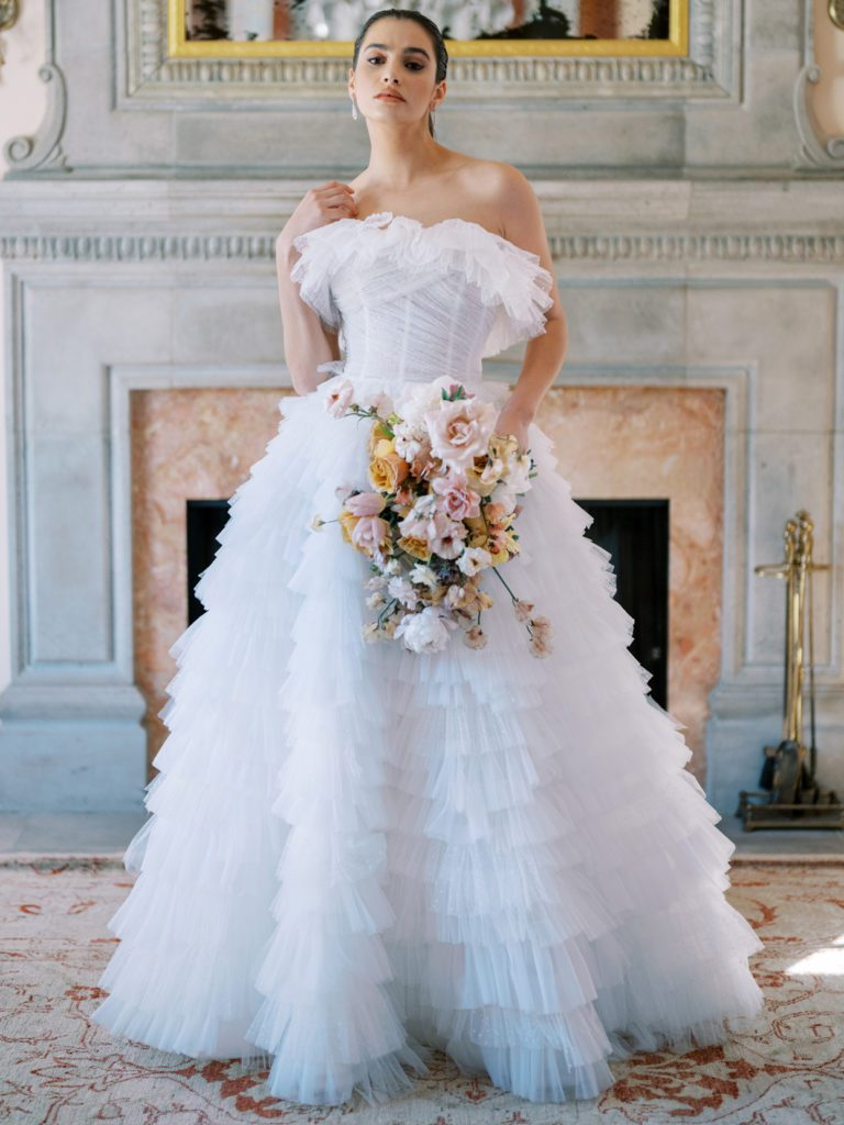 Bride wearing dramatic wedding ballgown with ruffled tiered skirt in front of fireplace