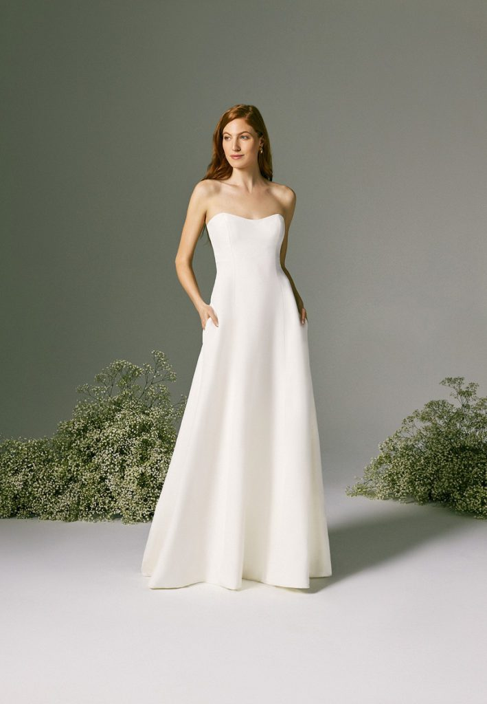 Bride wearing simple A-line wedding dress with large bushes of baby breathe behind her