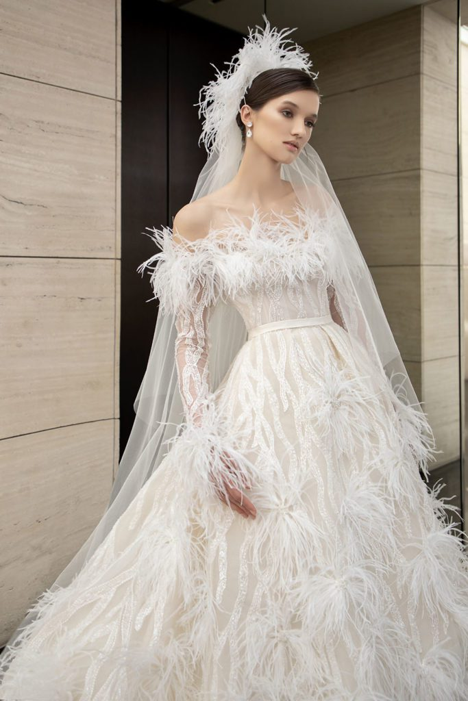 Bride wearing wedding dress with ostrich feathers, a dramatic long sleeve wedding dress