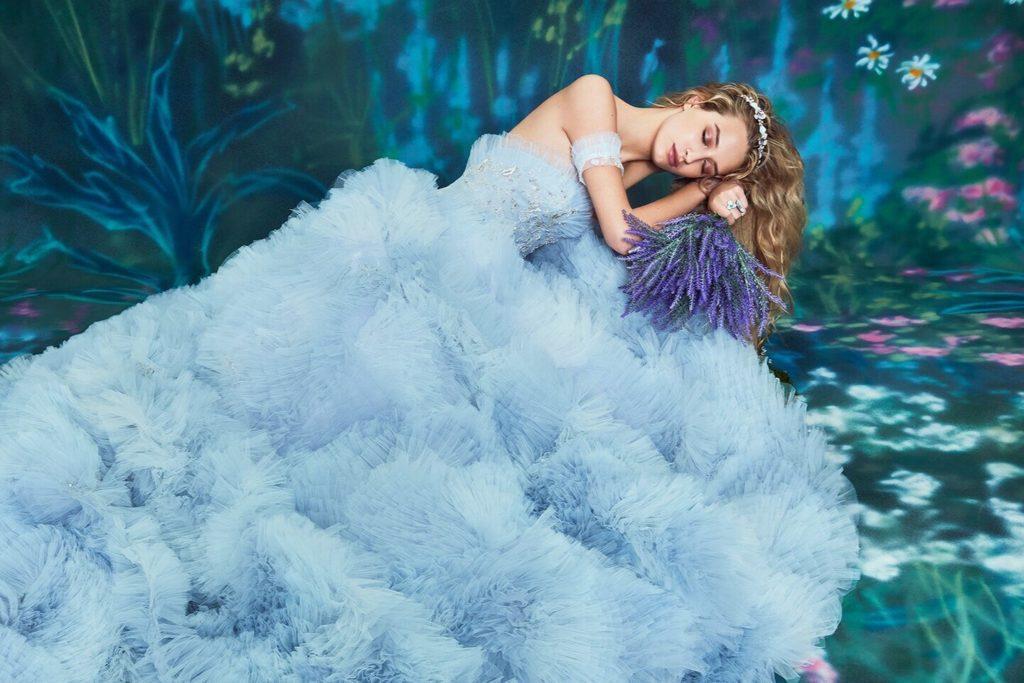 Bride laying down in beautiful ruffled blue wedding dress