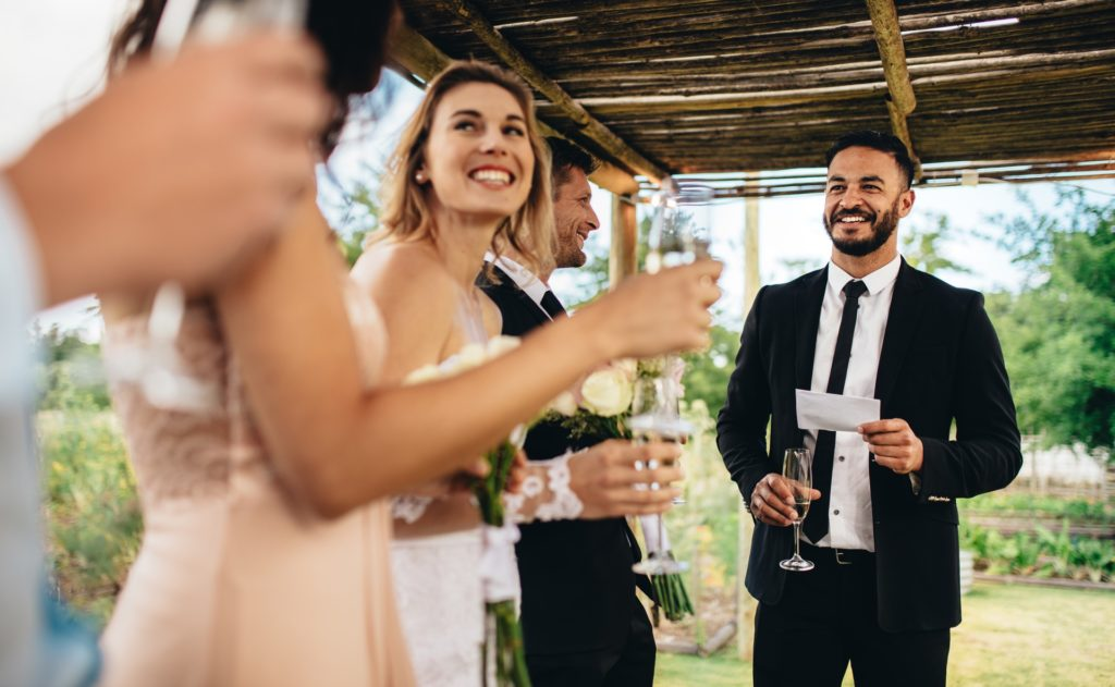 Guests making toast at wedding near smiling bride and groom