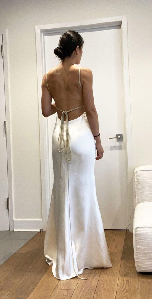 Bride standing in room wearing backless silk sheath wedding dress