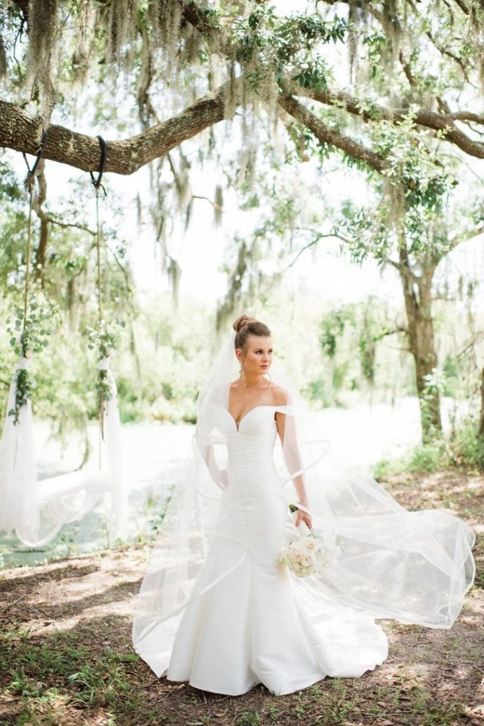 Beautiful bride standing under old oak tree with Spanish moss wearing off the shoulder simple wedding dress