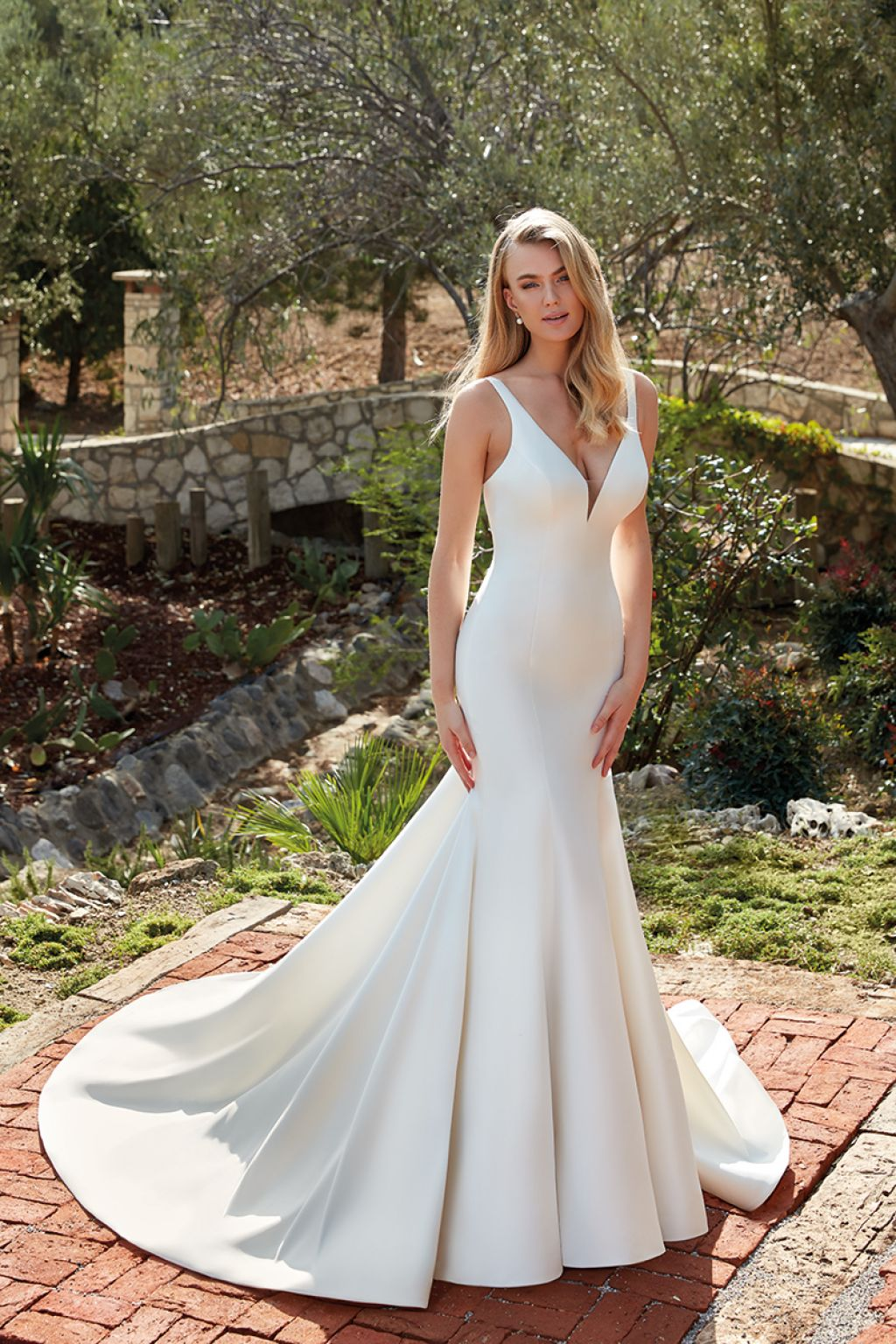 Bride with long blonde hair wearing simple V-neck wedding gown outside on brick path