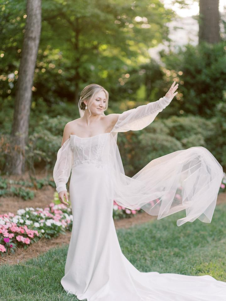 Bride standing in garden wearing whimsical wedding gown by Ines Di Santo waving