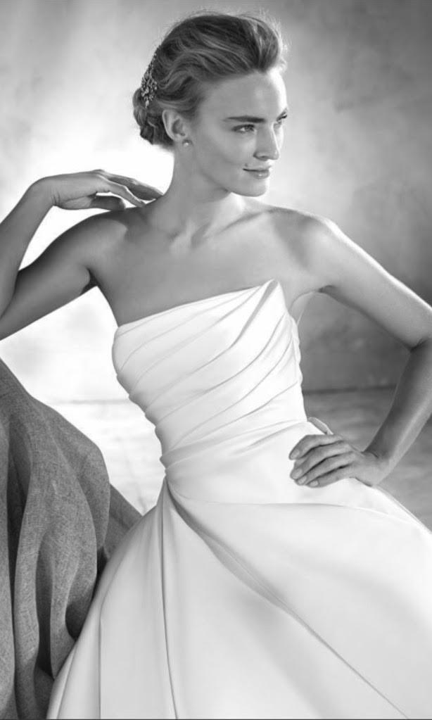 Woman sitting in a stunning Pronovias wedding dress with asymmetrical ruched bodice.